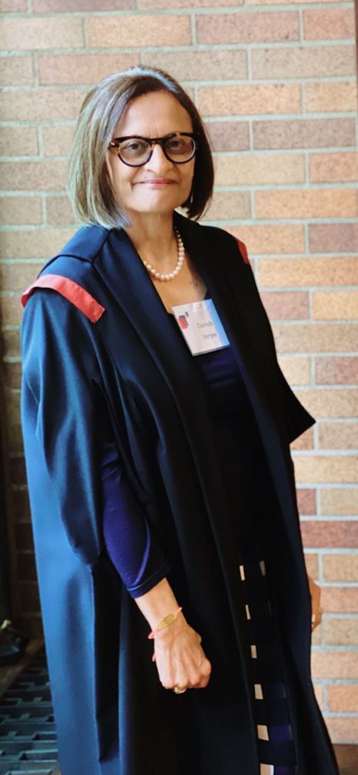 woman in graduation cloak in front of brick wall